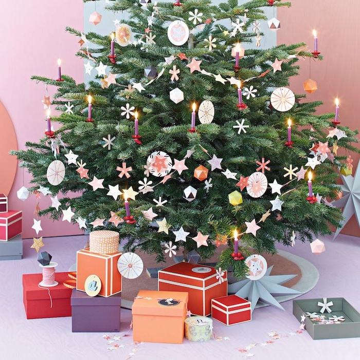 Echter Weihnachtsbaum geschmückt mit Anhängern und Girlanden aus Papier, Geschenkschachteln unter dem Baum