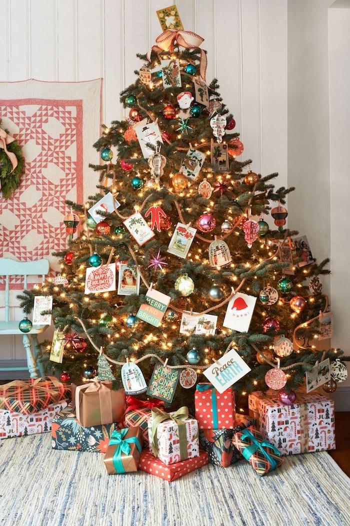 Großer Weihnachtsbaum geschmückt mit bunten Christbaumkugeln, Weihnachtskarten und Lichterkette