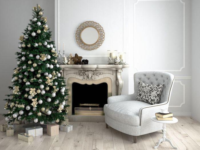 Weihnachtsbaum schmücken, mit weißen Weihnachtskugeln und goldenen Glöckchen, weißer Sessel, Bücher und Tasse Kaffee auf dem Couchtisch