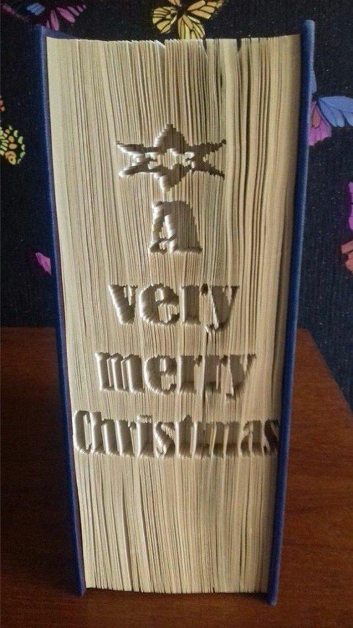 Eine Aufschrift A very merry Christmas, was auf Deutsch sagt, Fröhliche Weihnachten, gefaltete Bücher