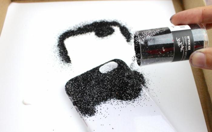mit schwarzem Glitter eine weiße Handyhülle bestreuen, Handyhüllen selbst gestalten mit Klebstoff