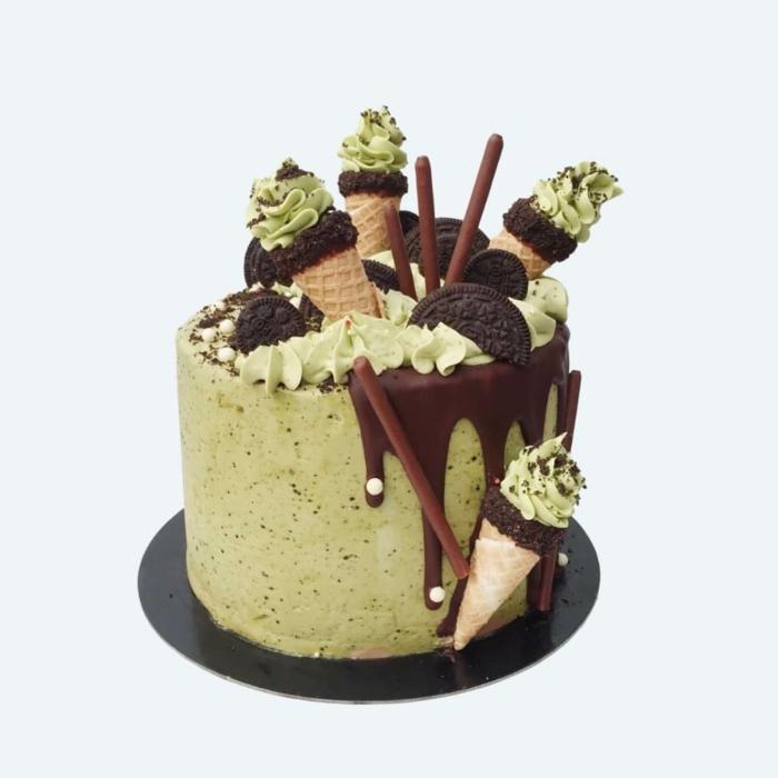 grüne Creme deckt dieser Kuchen, Oreo Keks Kuchen Rezept, Schokoladen, Bonbons und Waffeln als Dekoration