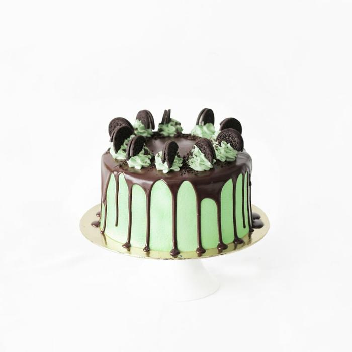 Oreo Keks Kuchen Rezept, Schokoladenglasur, halbe Kekse als Dekoration, eine grüne Torte