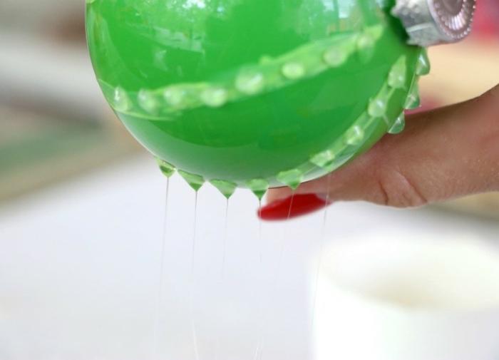 Weihnachtskugeln selbst gestalten, grüne Kugel mit durchsichtigem Nagellack