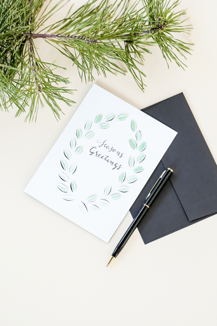 Tannenzweigen, weiße Karte, schwarzer Briefumschlag, Aufschrift mit Kugelschreiber, Weihnachtskarten Design
