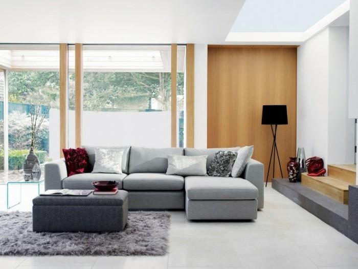 graues Ecksofa, grauer Teppich, eine schwarze Lampe in der Ecke, weißer Fliesenboden, Wohnzimmer Ideen Weiß Grau