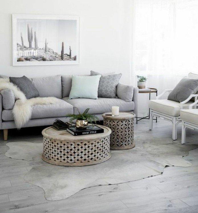 ein graues Bild, graues Sofa, ein weißer Teppich, runde Couchtische, ein schönes Wandbild