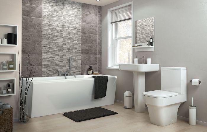 weiße freistehende badewanne und schwarze tücher und ein schwarzer teppch, badezimmer mit grauen wänden und mit kleinem fenster