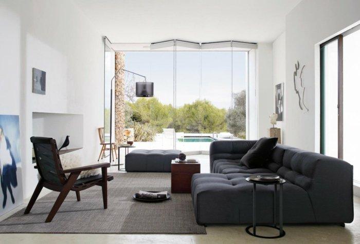 ein schwarzes Sofa, ein grauer Teppich, ein Glaswand, Wohnzimmer gestalten Weiß Grau
