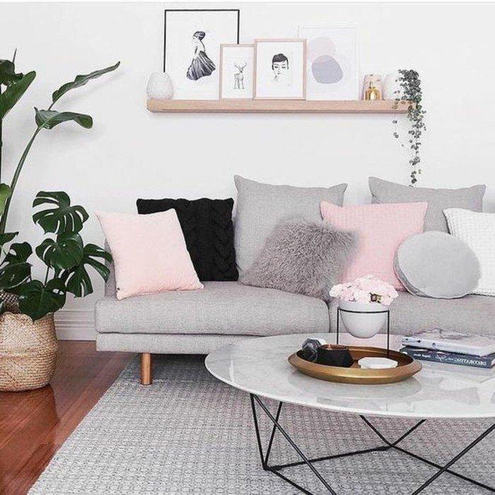 eine Leistne aus Holz voller Bilder mit bunten Rahmen, graues Sofa mit rosa Kissen, Wohnzimmer gestalten Grau Weiß