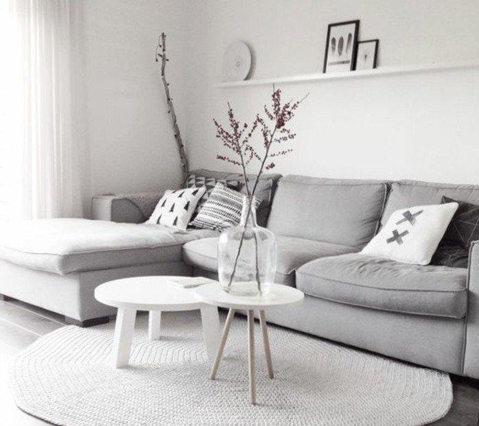 eine Vase mit trockenen Blumen auf kleinen Couchtischen, weißer runder Teppich, graues Sofa, Wohnzimmer in Grau Weiß