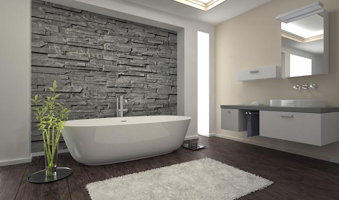 weiße freistehende badewanne und brauner boden aus holz mit einem kleinen weißen teppich, spiegel und badezimmer spiegelschrank
