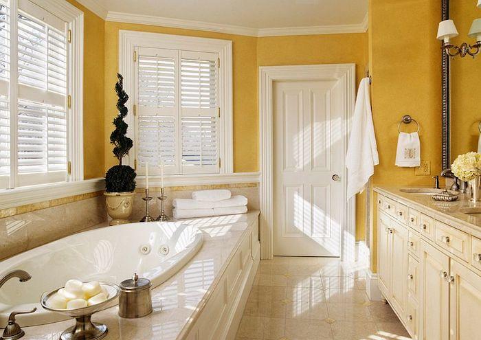 badezimmer gelb, ein badezimmer mit gelben wänden und weißen fenstern aus holz und eine große weiße badewanne und eine weiße tür