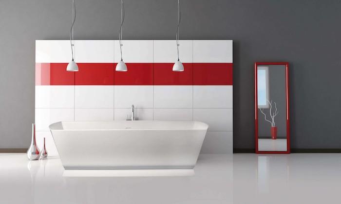 weißer boden und eine wand aus großen weißen und roten badezimmer fliesen, weiße freistehende badewanne und ein großer spiegel