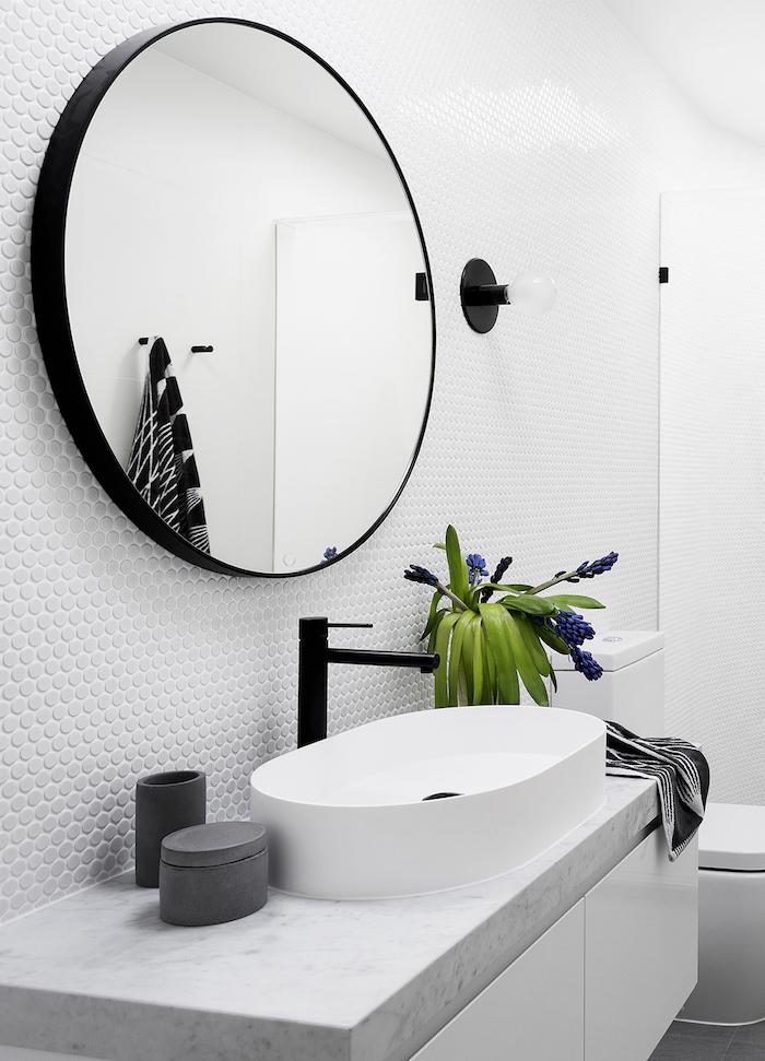 weiße wand aus weißen fliesen und ein großer schwarzer spiegel, ein weißes waschbecken, eine vase mit violetten blumen mit grünen blättern