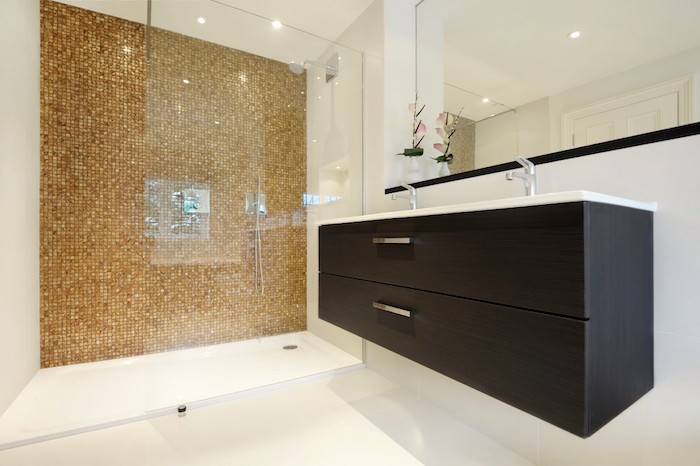 schwarzes waschbecken und ein spiegelschrank im badezimmer mit braunen und weißen fliesen