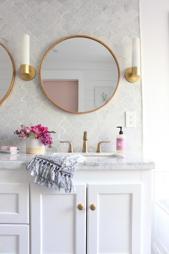 badezimmer regal, ein großer spiegel und zwei weiße badezimmer kerzen, waschbecken und kleine violtten blumen