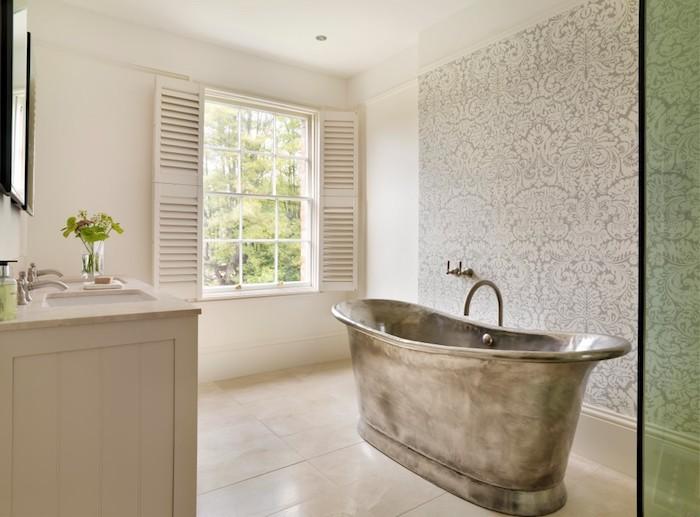 kleine bvase mit blumen und ein waschbecken, kleine graue freistehende badewanneaus metall im badezimmer mit weißen fenstern
