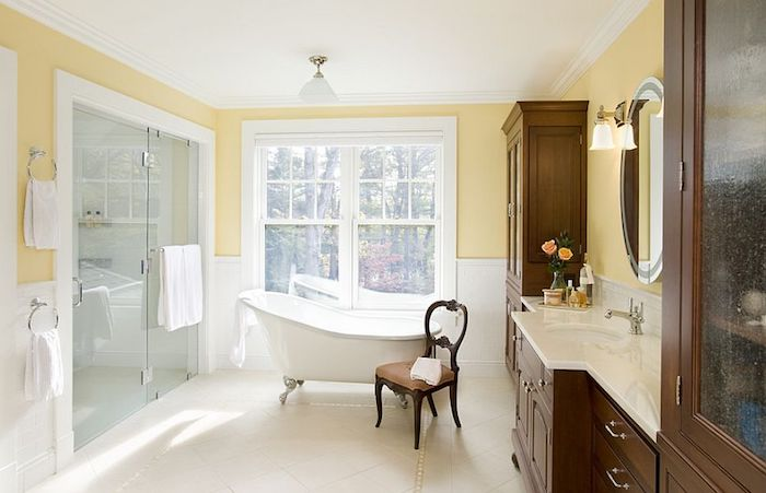 weiße kleine freistehende badewanne im badezimmer mit gelben wänden und großen weißen fenstern, ein brauner stuhl aus holz, badezimmer spiegelschrank