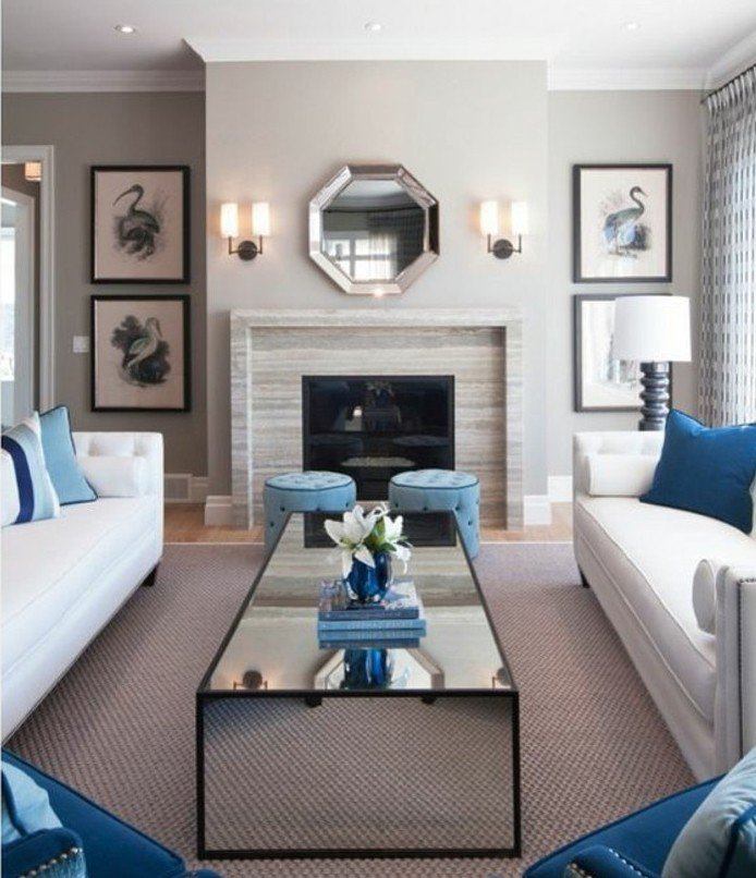 zwei weiße Sofas, ein Glastisch mit Blumen in der Mitte, Wohnzimmer Weiß Grau, ein Spiegel