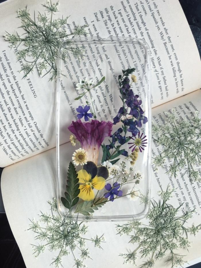 silikon Handyhülle selber gestalten Samsung mit getrockneten und gepressten Blumen in lila und gelb, offenes Buch,