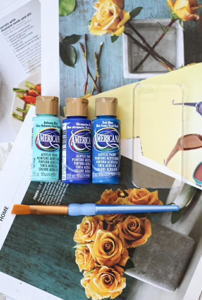 Handyhülle designen mit Acrylfarben in blauen Töne, Blumen in gelb, durchsichtige Handyhülle, blauer Pinsel