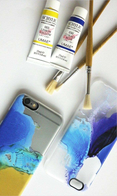 Personalisierte Handyhülle, Acrylfarben in blau und gelb, drei Pinsel, zwei Handgemalte Handyhüllen