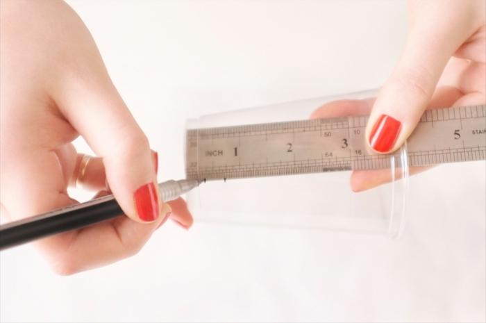 Plastik Becher mit Lineal zwei Mal markieren, Hand mit rotem Nagellack und Ring, Handyhülle selber gestalten,