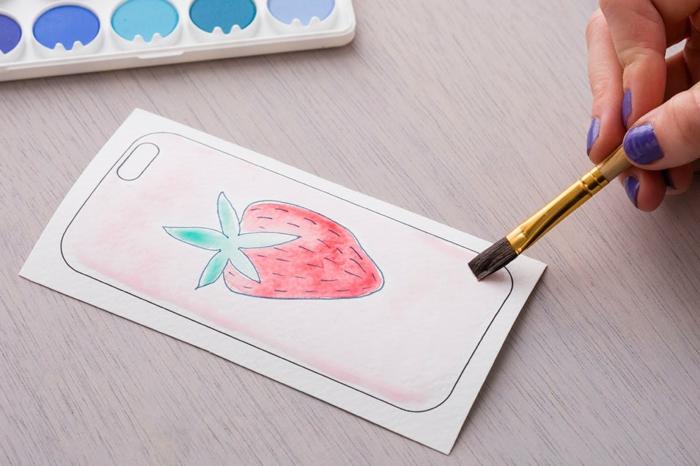 DIY Anleitung für Handyhülle selbst designen, Zeichnung von Erdbeere bemalt in pink und grün, Hand mit lila Nagellack