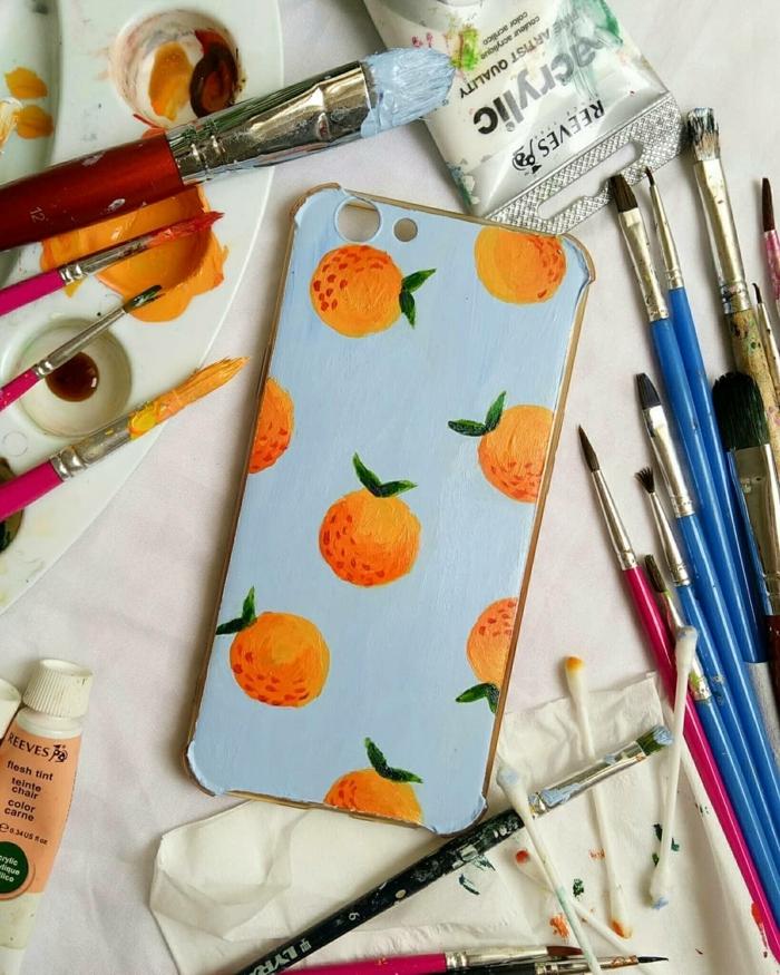 handyhülle personalisieren, handgemalte hülle in blauem Hintergrund und Orangen, kleine und große Pinsel
