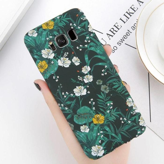 Handyhülle selber gestalten Samsung, grüne Hülle mit Blumenmotive in weiß und gelb, Hand mit dunklem Nagellack