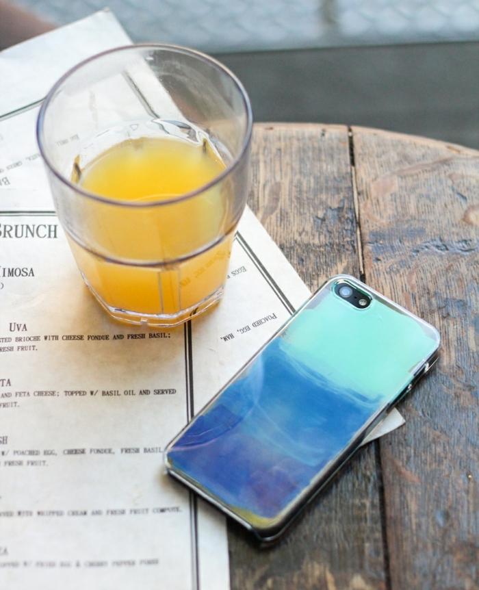 Silikon Handyhülle selber gestalten, Acrylfarbe in blauen Töne, Glas mit Orangensaft, Tisch aus Holz