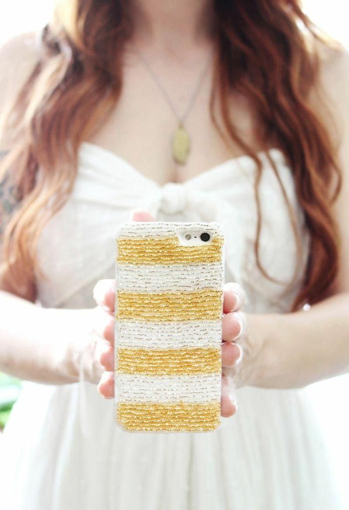 Hülle selbst gestalten mit Glasperlen in weiß und gold, Frau mit braunen Haaren und weißes Kleid