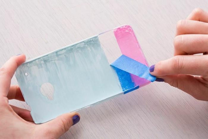 Hand mit Nagellack in lila, Entfernen vom Band von Handyhülle, Handyhülle designen, in pink und hellblau