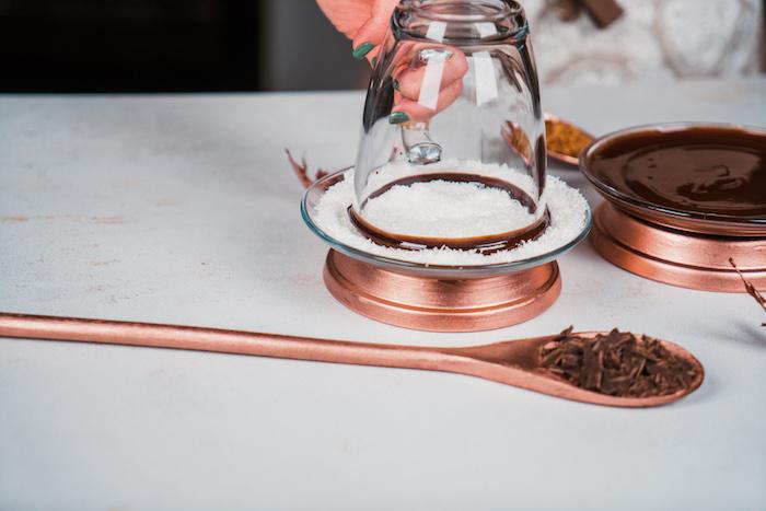 Den Tassenrand in Kokosraspel tauchen, heiße Schokolade dekorieren