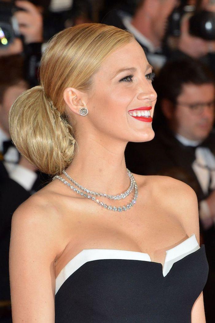 Niedriger Dutt zum Nachstylen, lange blonde Haare, schwarzes trägerloses Kleid mit weißer Kante, roter Lippenstift, silberne Halsketten mit Kristallen