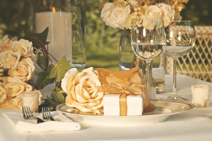 tischdeko zur hochzeit mit einer weißen decke und mit kerzen und vielen goldenen gelben rosen, hochzeit bilder