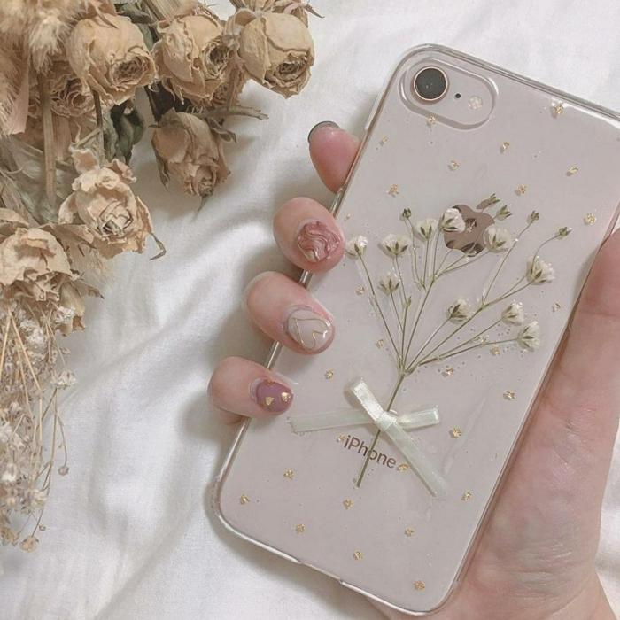 Handyhülle selber gestalten, getrocknete und gepresste weiße Blumen, iphone 6s handyhülle, Hand mit Nagellack in Nude