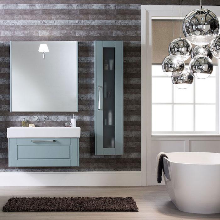 ein spiegel und waschbecken im badezimmer mit einer kleinen weißen freistehenden badewanne, badezimmer lampen