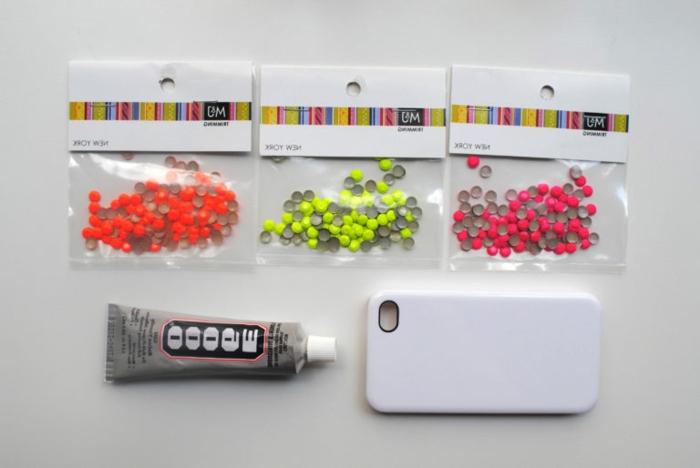 drei Päckchen mit Glasperlen, Klebstoff und eine Handyhülle, Materialien für Handyhülle designen
