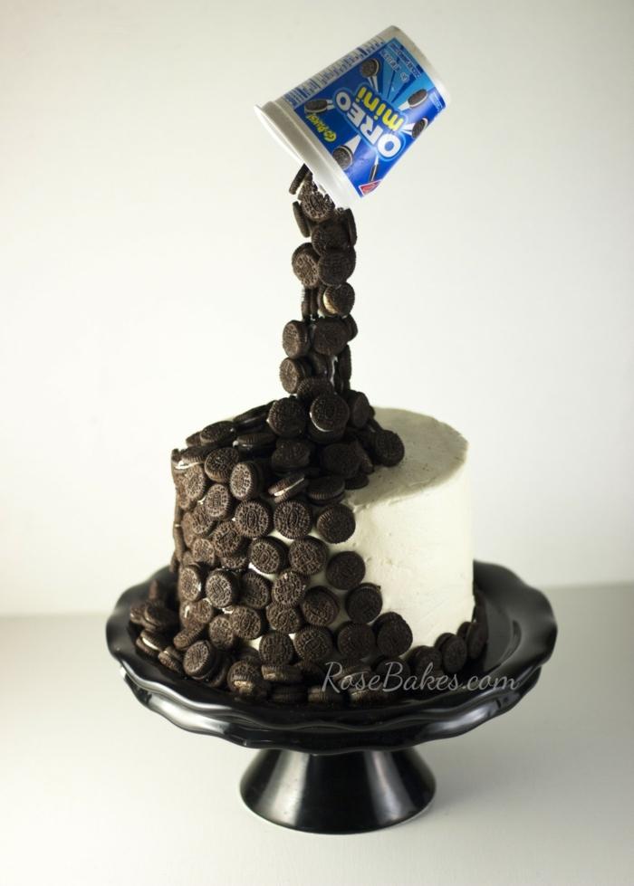 Oreo Keks Kuchen Rezept, Mini Oreos fallen von einem Bechen auf Torte mit weißer Creme