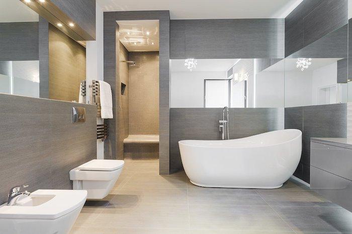 weißes waschbecken im badezimmer mit grauen wänden und spiegeln, eine weiße freistehende badewanne