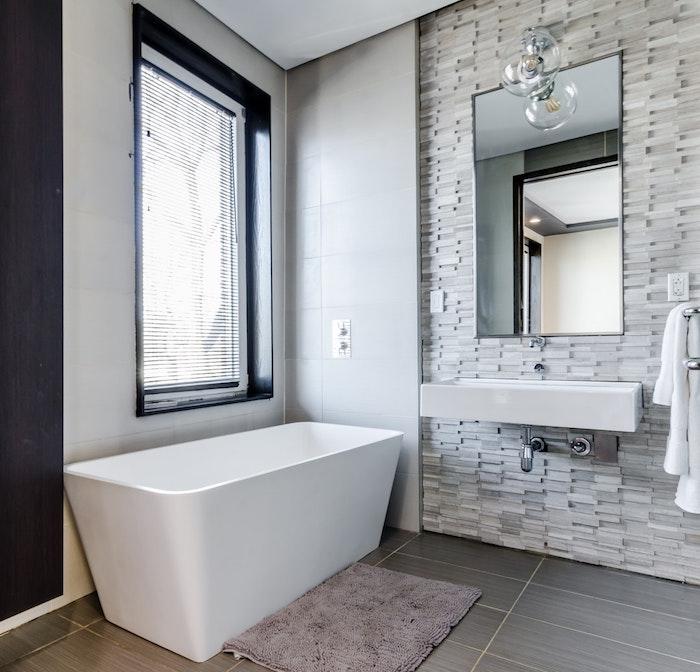 weiße freistehende badewanne im badezoomer mit einem fenster und spiegel, boden aus grauen badezimmer fliesen