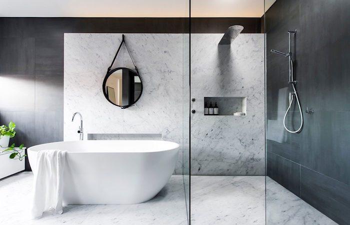 ein spiegel und kleine weiße freistehende badewanne im badezimmer mit weißen und schwarzen wänden und badezimmer fliesen