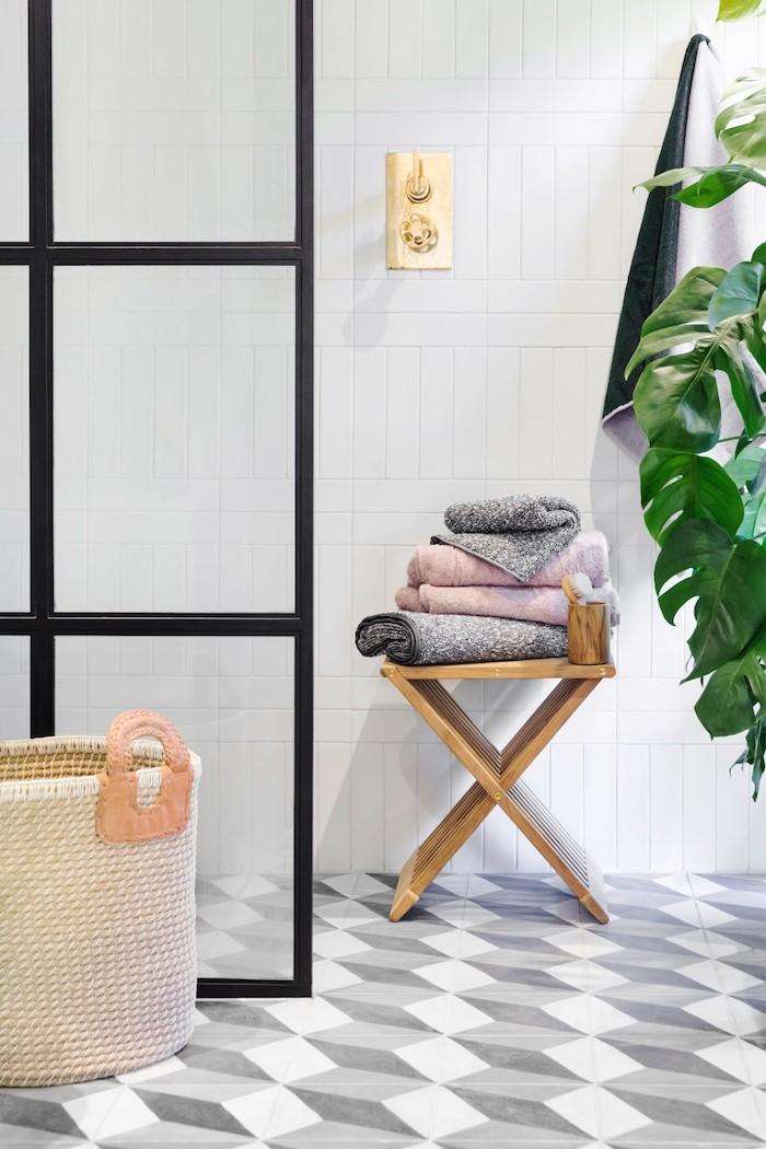 boden mit grauen und wei0en badezimmer fliesen und ein brauner stuhl aus holz, weiße wand aus vielen weißen badezimmer fliesen und eine grüne pflanze mit grünen blättern