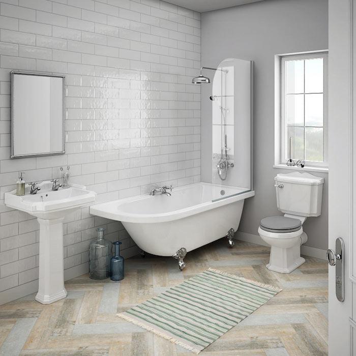 boden mit einem grünen teppich im badezimmer mit weißen wänden mit weißen badezimmer fliesen, eine weiße badewanne und weißes waschbecken und ein spiegel