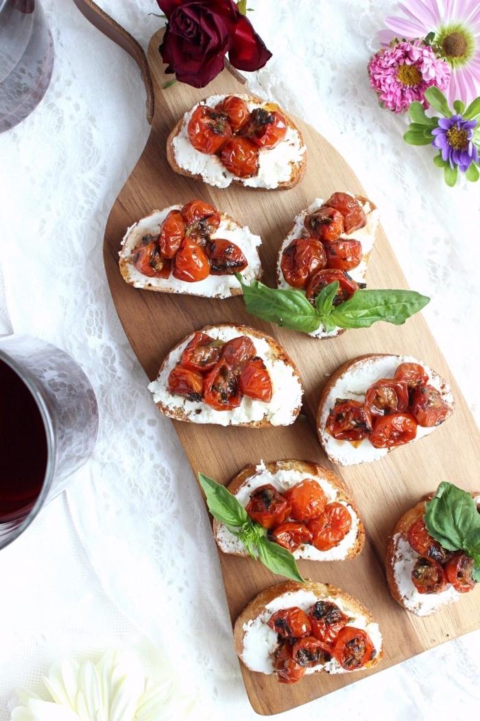 langes holzbrett, bruschettas mit cherry tomaten, gewürz und basillikum, kochen für gäste
