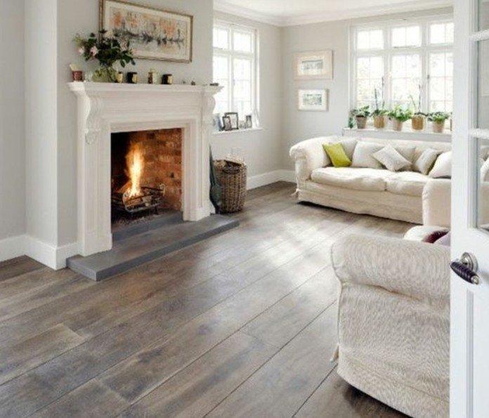 ein gemütliches Wohnzimmer Weiß Grau, ein Kamin mit Feuer, weiße Wohnzimmermöbel