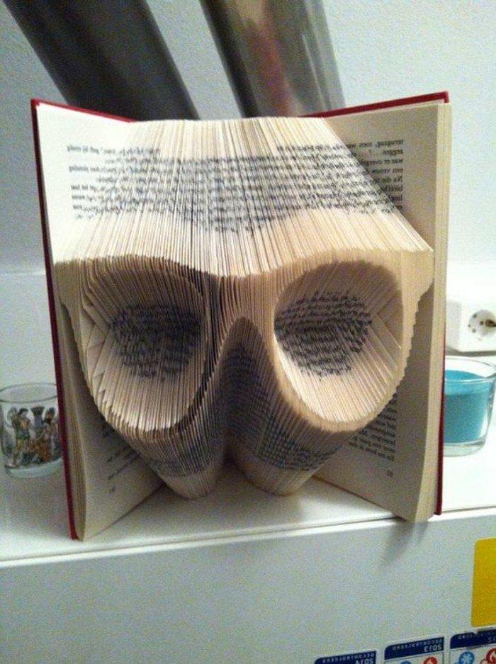 große Lesebrillen mit dicken Rahmen, gefaltete Bücher, ein Buch mit rotem Briefumschlag