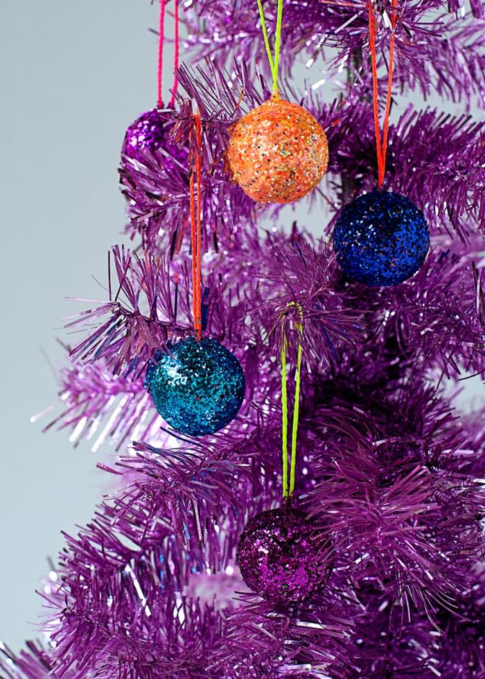 blaue Kugeln, orange Kugel und lila Kugel, Weihnachtskugeln bemalen und auf lila künstlichen Christbaum hängen